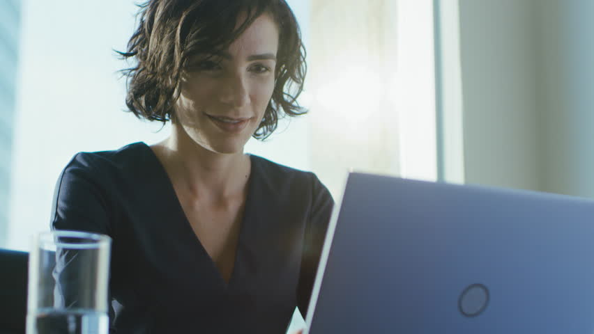 Portrait of the Focused Female CEO Working on a Laptop. Happy Successful Businesswoman Doing Her Important Business Job Beautifully. Shot on RED EPIC-W 8K Helium Cinema Camera. | Shutterstock HD Video #1016145721
