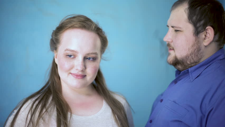 Overweight male whispering compliment in girlfriends ear, feelings expression