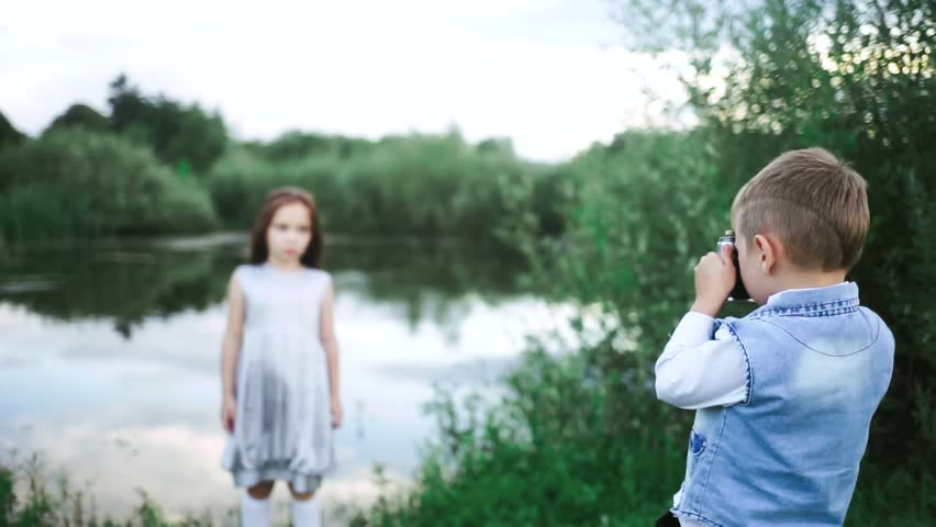 Brother takes pictures of his sister in nature. Children learn to take pictures. Brother and sister on a walk. A little boy takes pictures of a girl. Baby with a camera in his hands