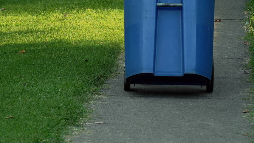 Man moving a recycling bin outside #1016215231