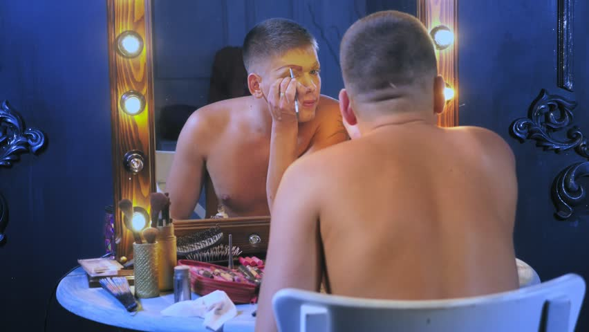 travesty-diva. The concept of a transvestite. Man-actor turns into a woman. a man applies a make-up on his face. in the room in front of the mirror. 4k, shooting steadicam