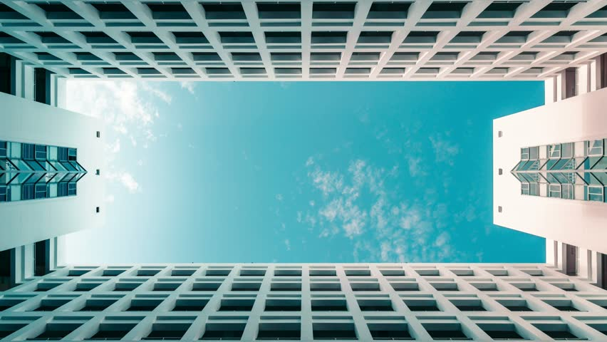 Timelapse of modern symmetrical architecture building with blue cloudy sky, abstract low angle clouds skyscaper shot