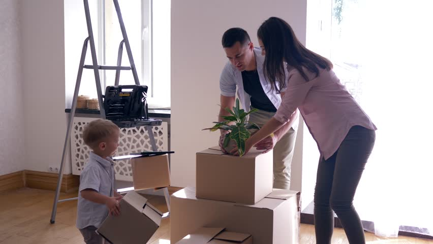 Moving to new home, happy family with little child bring things to new house after repair and raise their hands up for joy | Shutterstock HD Video #1016251291