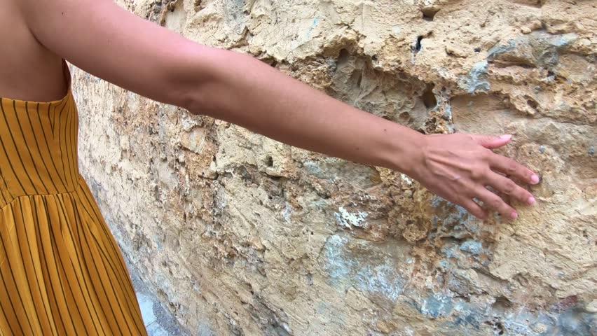 Woman walks and grazes hand on stone wall. 4K