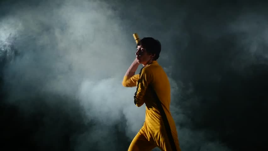 Costume Bruce Lee. the young man expertly twirling nunchaku.on black background. smoke, yellow clothing. Slow motion. Bruce Lee style.