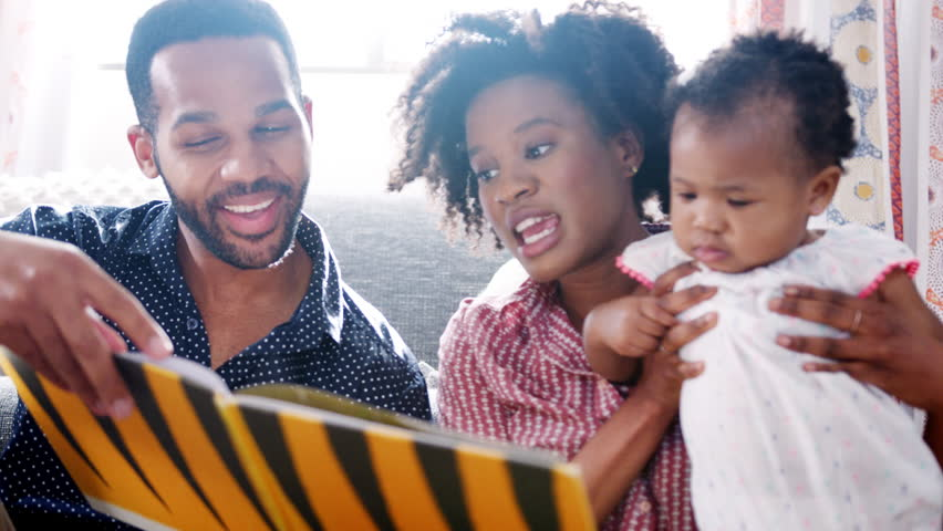 Parents Sitting On Floor And Reading Book With Baby Daughter At Home   Shutterstock HD Video #1016266291
