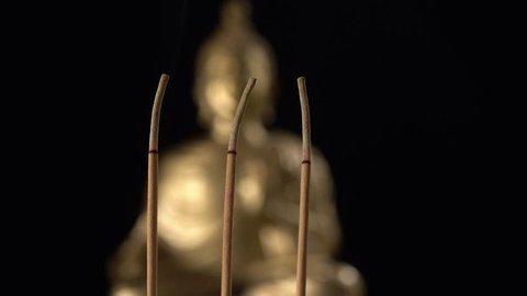 3 incense sticks burned front Buddha image