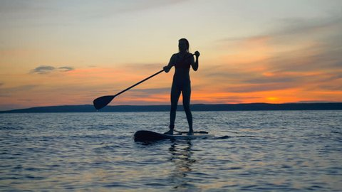 A woman is floating on a paddleboard during sunset. Active lifestyle concept.