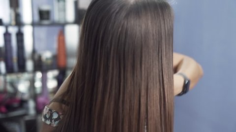 A close-up slow-motion shot of a girl in a beauty salon admires her long straight shiny hair after keratin straightening. The concept of hair care in the salon, keratin, hair straightening.