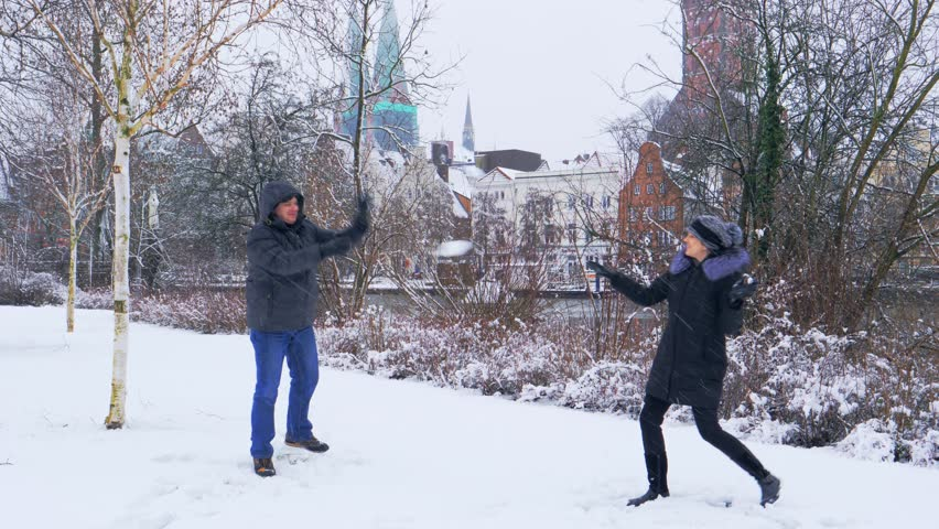 Couple playing snowballs, cheerful winter mood, snow covered road in park. Lubeck city in winter time