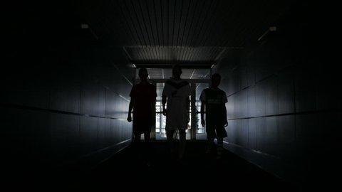Three football players are walking along a dark tunnel to the football field.