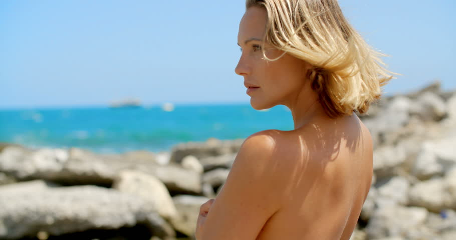 Nude Blond Woman Staring Into the Distance at Ocean on Rocky Beach with Breeze Blowing in Hair