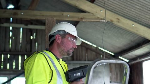 Construction Worker Undertakes Property Development Work In Progress. A Variety Of 4K Camera Angles Available.