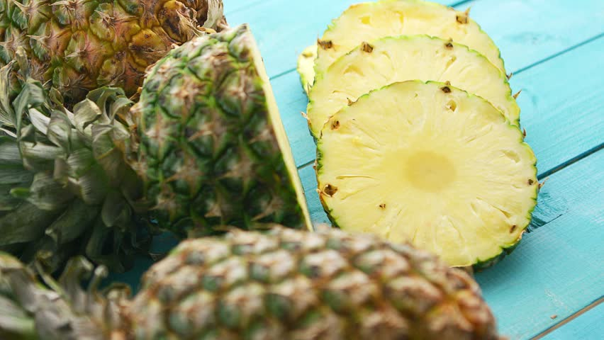 From above shot of composed unpeeled slices of freshly cut and served pineapple with juicy flesh on blue wooden surface | Shutterstock HD Video #1016361061