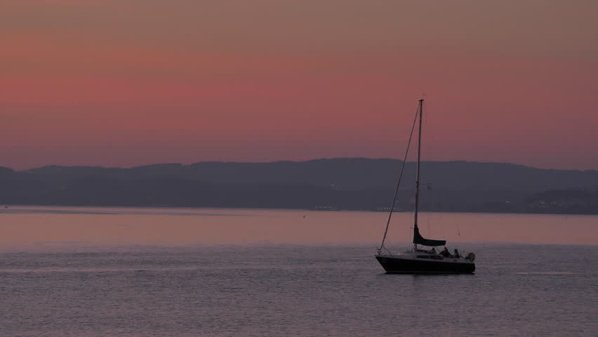 sailboat in sunset near harbor Altnau. two carferrys at German shore at horizon. lake Bodensee, CH Switzerland. 11th Sept.2018