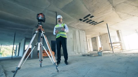 Architect with tablet uses a walkie talkie, standing in the unfinished building.