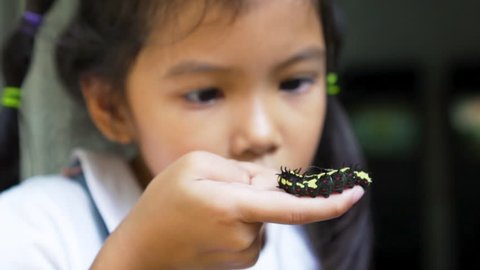 Black caterpillar crawling on girl hand, she playing and happiness, slow motion shot