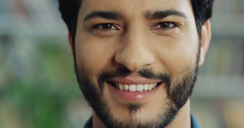 Portrait of the handsome young Arabian man with a beard smiling cheerfully to the camera. Close up of the face.