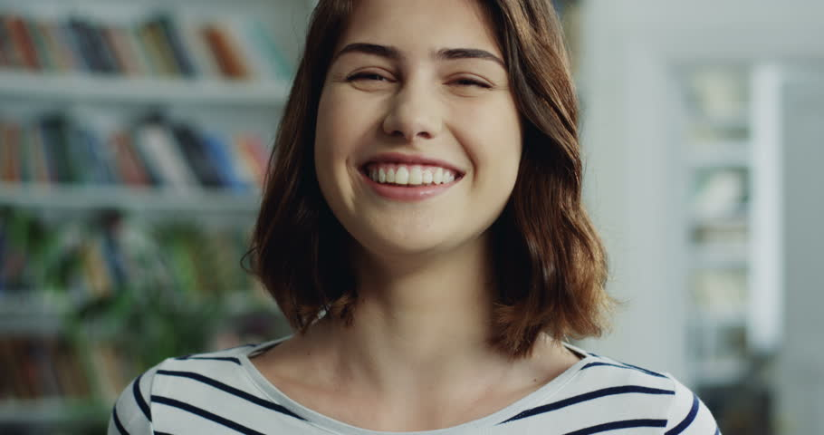Portrait shot of the good looking Caucasian young woman standing in front of the camera and laughing. | Shutterstock HD Video #1016396101