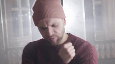 Young bearded man dressed in brown knitted sweater and pastel sock cap is rapping with hand gesturing, looking at camera and stepping back and forward during rap in bright room.