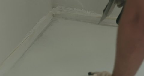 Slow motion closeup male worker applying micro concrete plaster coating on the floor with a trowel