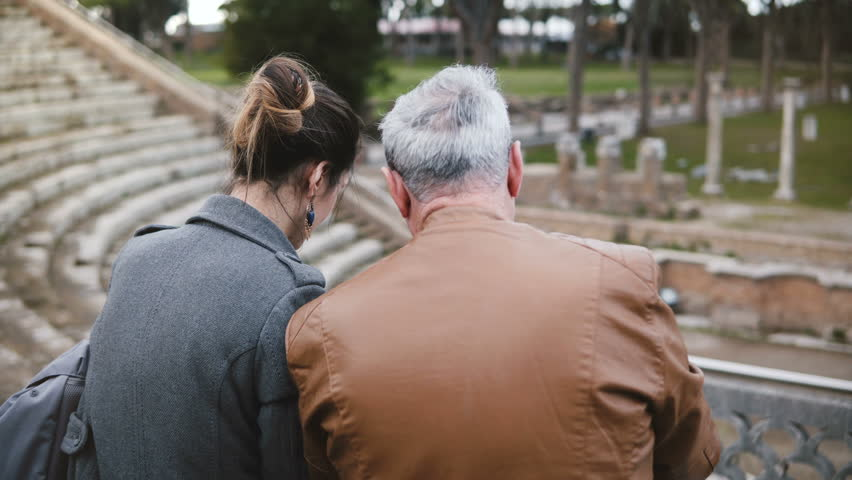 Back view of happy young European girl sitting together with older man talking at ruins of Ostia amphitheater in Italy. | Shutterstock HD Video #1016414971