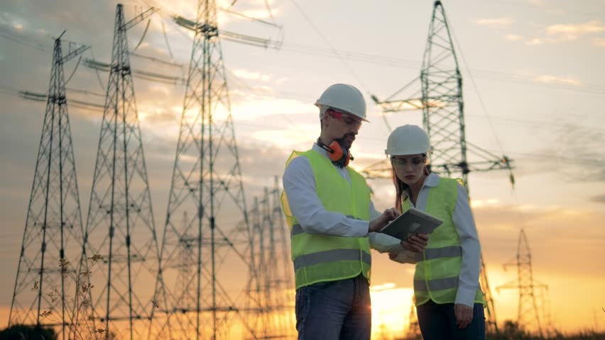 Electricity workers look at a blueprint on paper, close up.