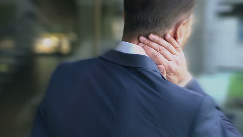 Man in suit suffers from neck pain, passive lifestyle causes spinal problem