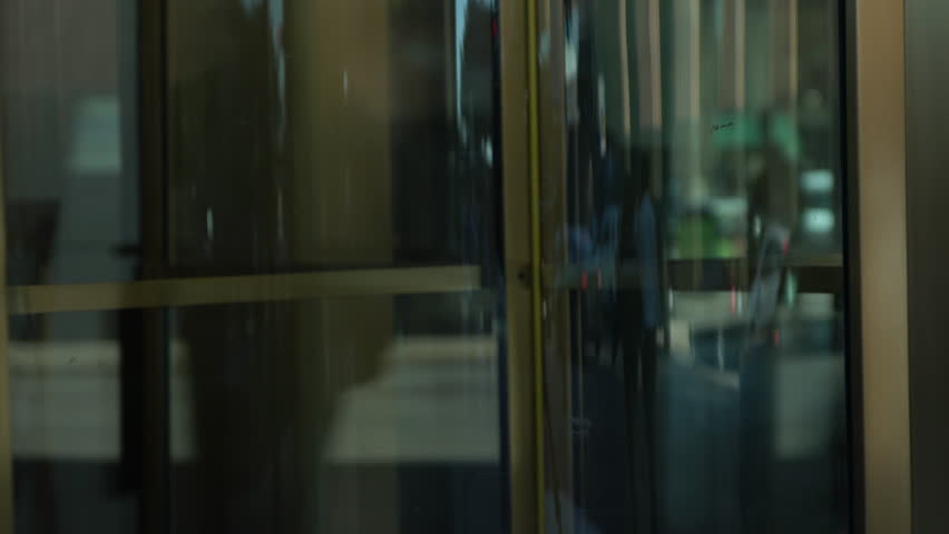 Close up of hands pushing a revolving glass door in a downtown city setting.