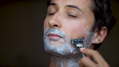 Face of the man during shaving Beard is processed by foam for shaving Hair on beard removes razor