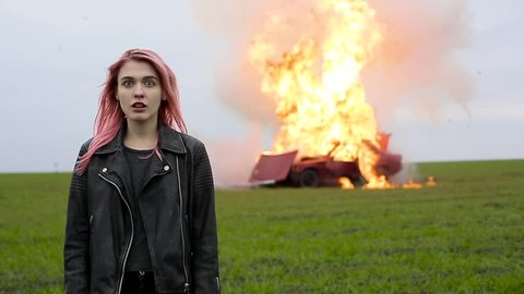 Young beautiful girl with pink hair and in a leather jacket stands on the background of an exploding car, a hipster and a burning car, car explosion