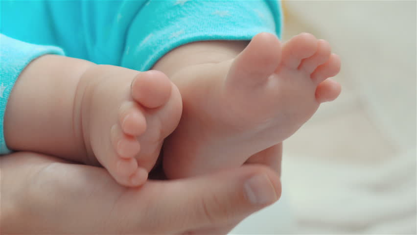 Parent holding babys feet. Mother gently stroking her child's feet #1016515561