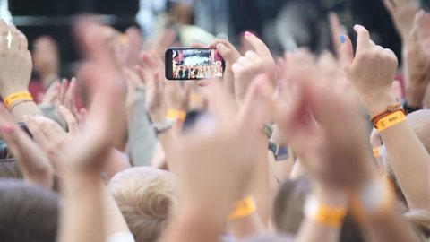 Group Of Young People Enjoying Outdoor Music Festival. Close-up rear view of crowd on concert. Funny people shoot a concert on the phone