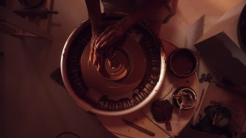 Process of shaping clay dish with wide edges on rotating potter's wheel having small tray table with ceramic pot with water and pottery tools in dark light studio.