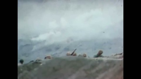 CIRCA 1945 - US Marines pinned down on Iwo Jima's Green Beach put out a call for help, and US Navy planes bomb Japanese forces.