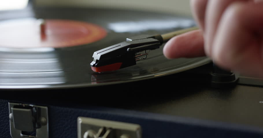 Man fumbles to remove retro record player needle from vinyl - close up scratching record