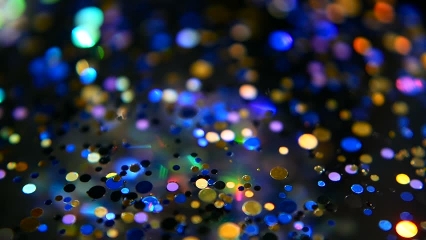 Defocused shimmering multicolored glitter confetti, black background. Party, magic, imagination. Rainbow colors, sparkle circles. Holiday abstract festive texture of shiny blurred bokeh light spots. | Shutterstock HD Video #1016620171