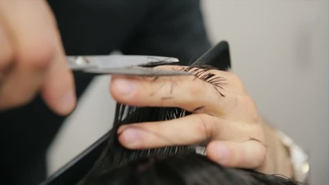 Barber Cuts the Hair in the Barbershop. Man hairdressing with scissors cuts the Hair. Slow Motion. Close Up