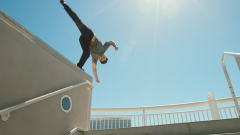 Slow motion parkour athlete in urban city doing extreme front flip off ledge with lens flare