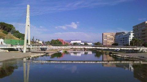 Pedestrian bridge in spanish coastal city near sea under bright sun - fly over
