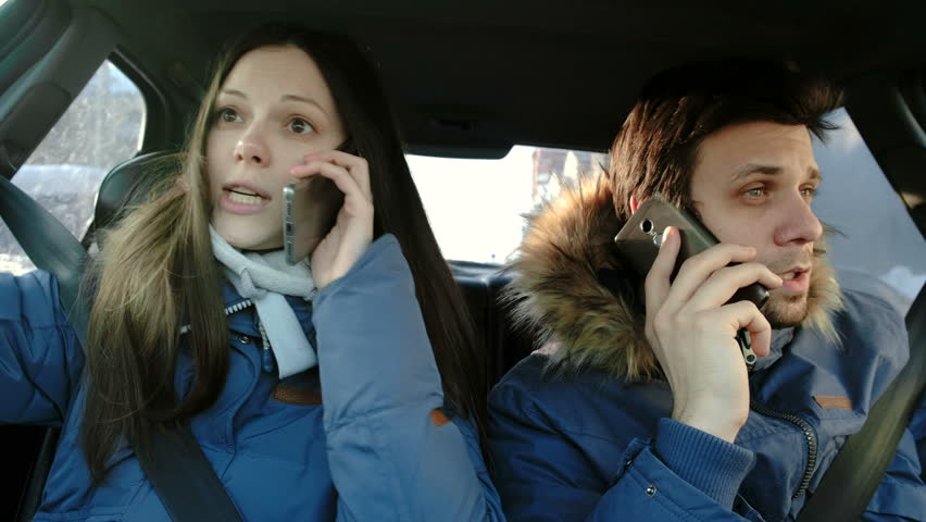 Man and woman swearing their cellphones and hysterical laughing sitting in car. #1016673181