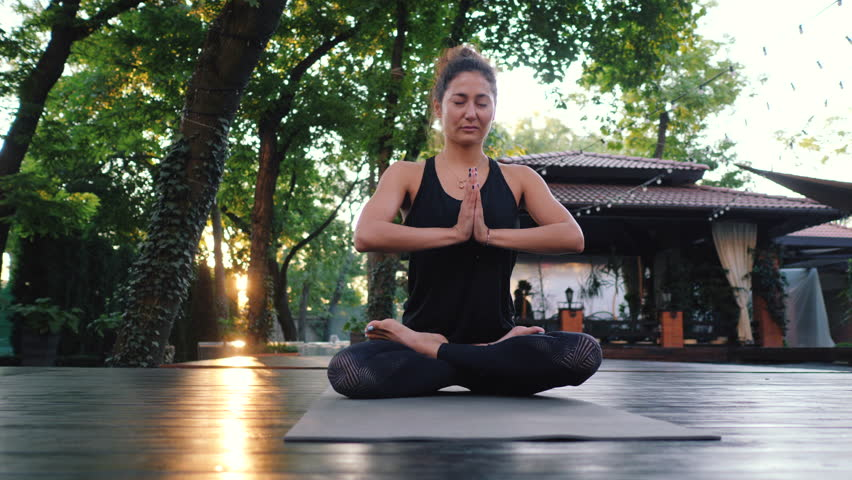 Pretty woman with oriental face practicing yoga, namaste gratitude mudra alone in tropical island. Girl in lotus pose. Religion, purity, resignation, spirituality concept. Padmasana. | Shutterstock HD Video #1016674921