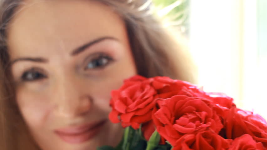 Portrait of a young beautiful woman with a bouquet of flowers of red roses. #1016677201