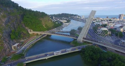 AERIAL FLYING OVER A TRAIN PASSING BY A BRIDGE ABOVE THE RIVER AT BARRA DA TIJUCA RIO DE JANEIRO BRAZIL