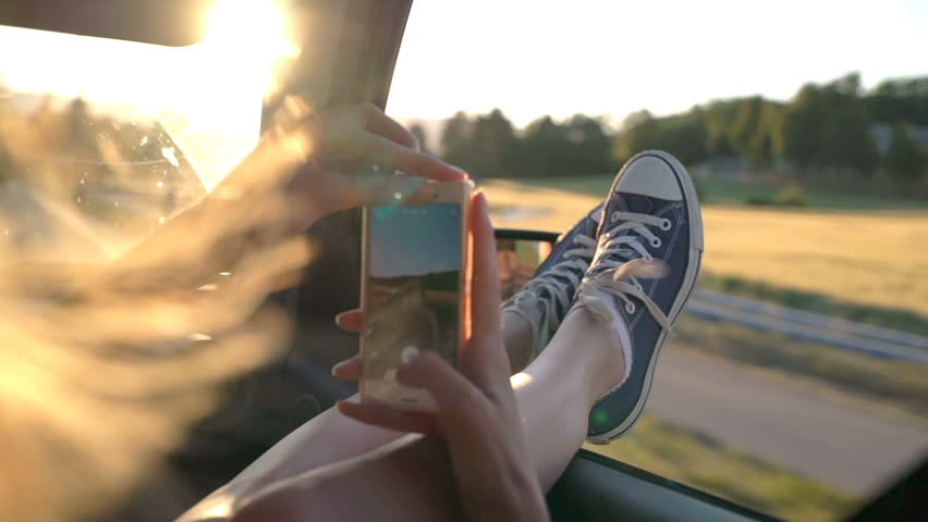 A young redhead woman enjoys traveling in a car by sticking out her legs in an open window and taking pictures using the phone. Slow motion. | Shutterstock HD Video #1016690851