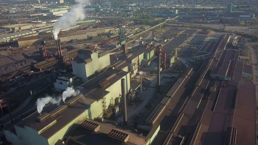 Aerial drone flight over a steel plant.  Train cars of molten steel are flushed with water producing giant plumes of steam. | Shutterstock HD Video #1016693911