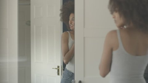 African American woman getting dressed at home in bedroom