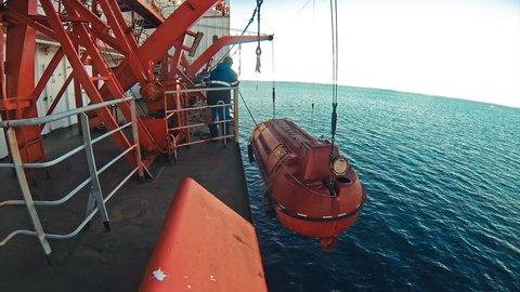 Orange lifeboat for emergency evacuation loading for safety