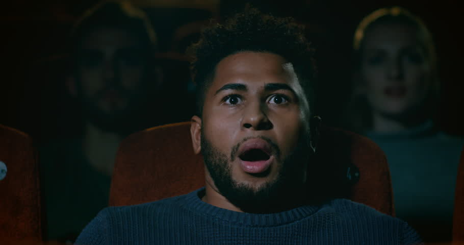 Young man at the movie theatre watching a scary movie. Reacts with shock and a large gasp. Slow motion | Shutterstock HD Video #1016720161