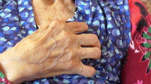 Elderly woman having heart attack, chest pain. Close-up shot